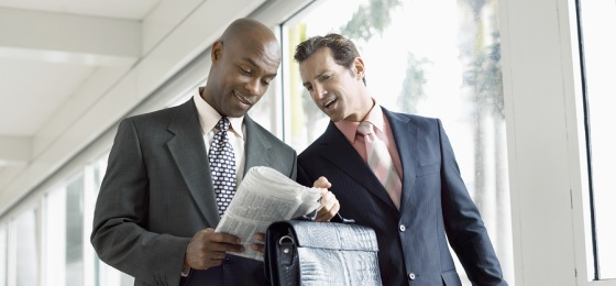 Multi ethnic businessmen reading newspaper together in office